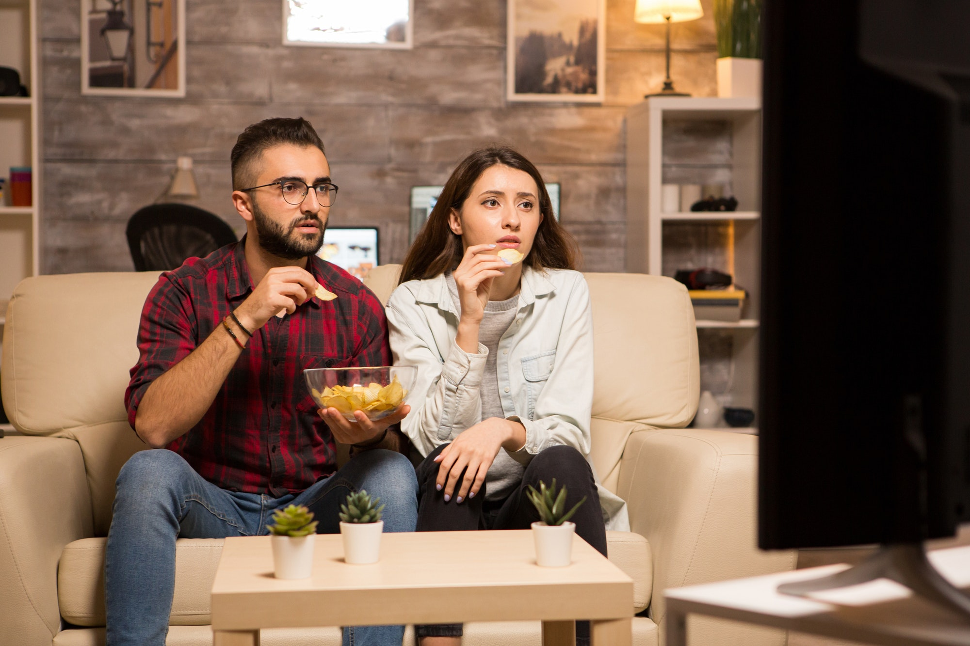 Beautiful young couple looking worried at tv while watching a movie