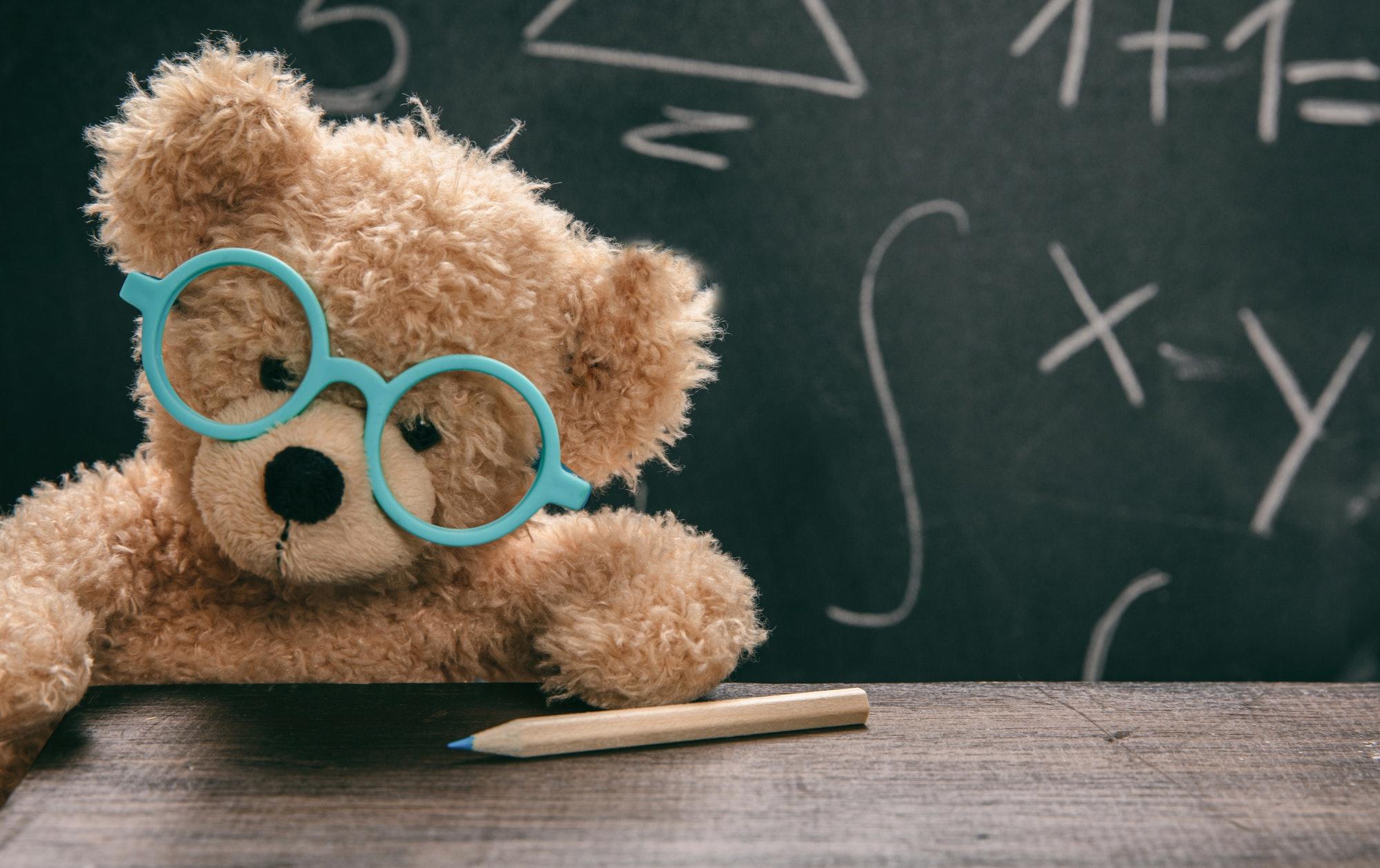 Math test. Cute teddy wearing glasses and black chalkboard