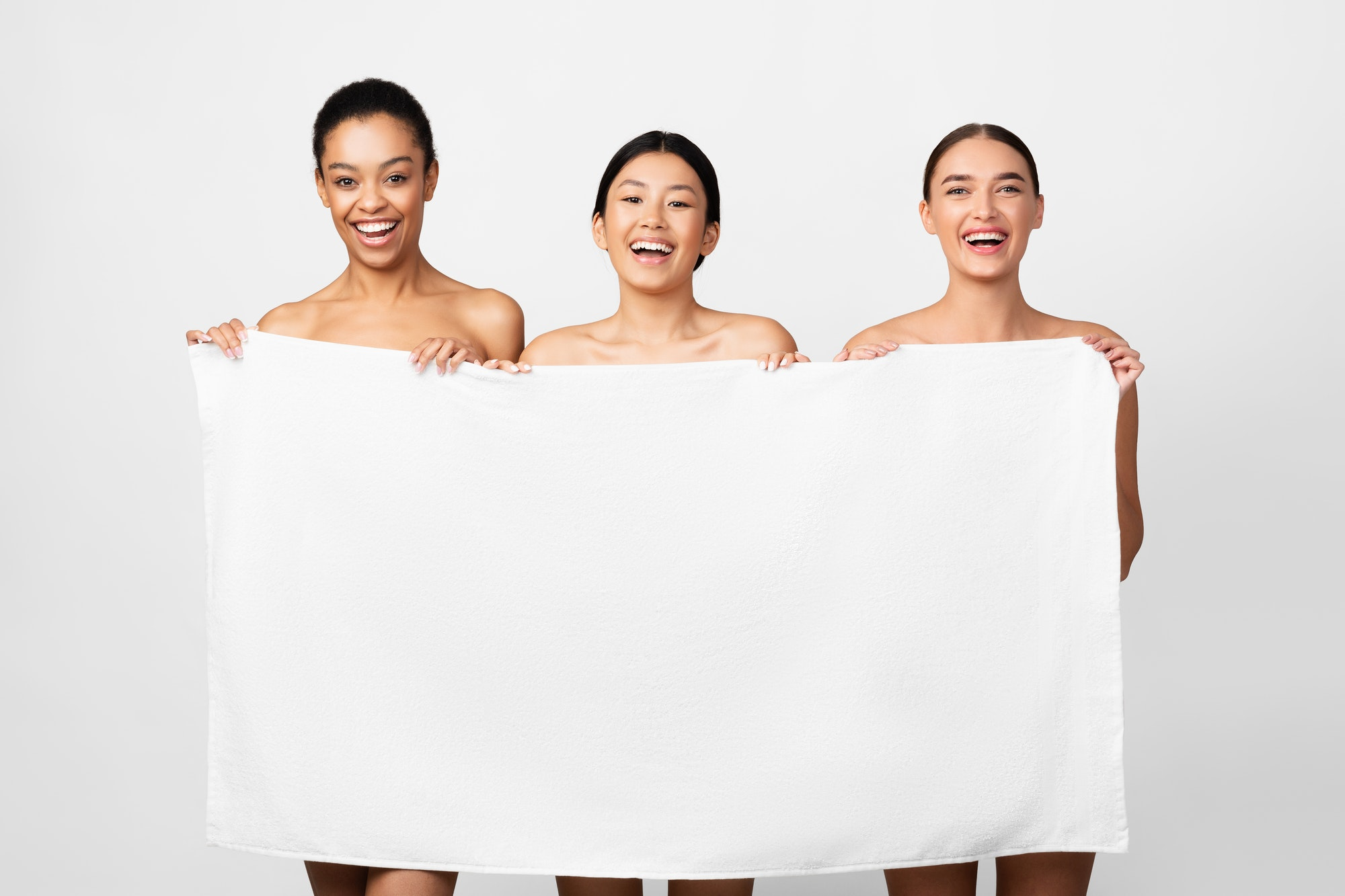 Three Multiethnic Women Holding Bath Towel Posing, Studio Shot