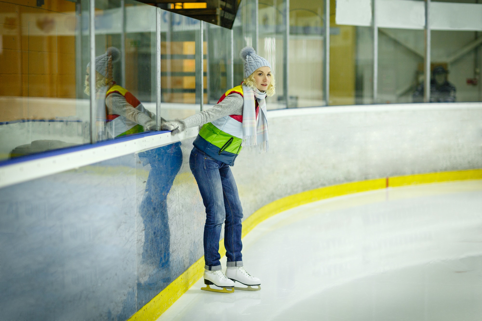 Beautiful girl in winter clothes and skates on ice rink