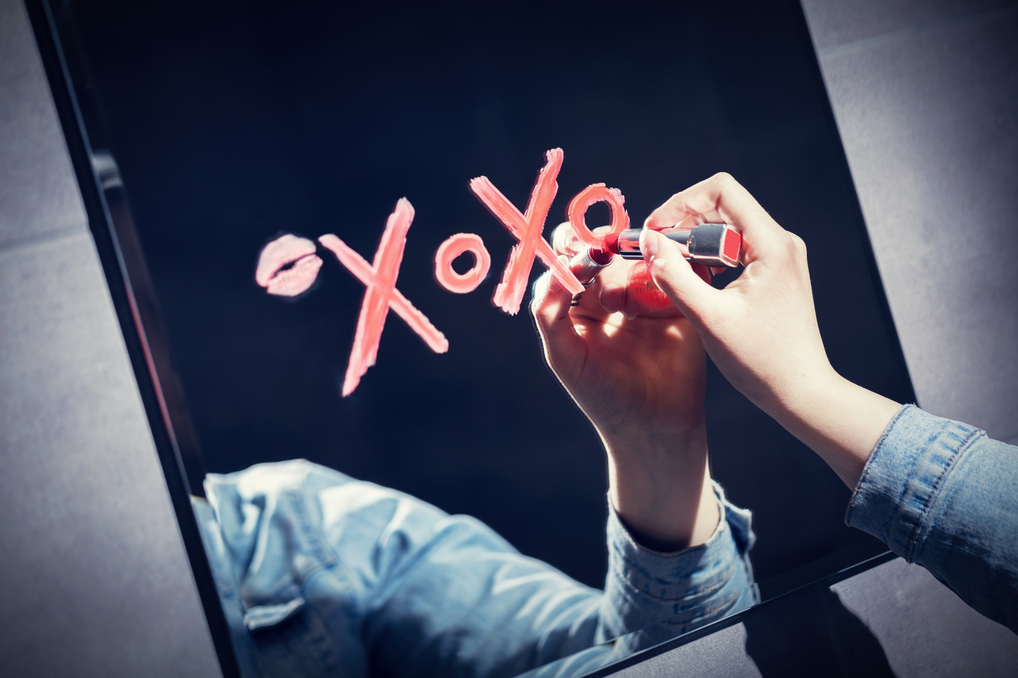 Woman writing xoxo on a mirror with red lipstick.